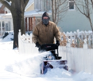 Brian Matzen removes snow from his sidewalks along Grant Street Sunday. Snow cleanup in W. County