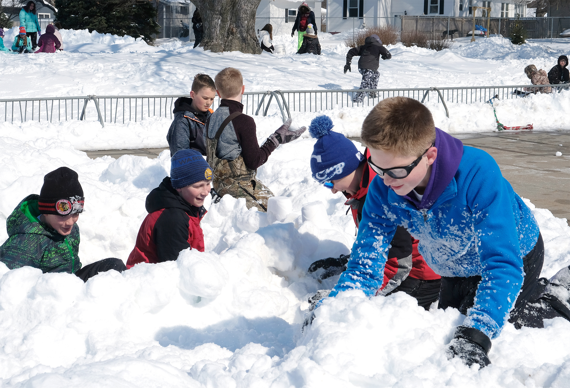 Boys build snow forts in the snow.
