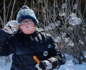 Boy in snow blows bubbles