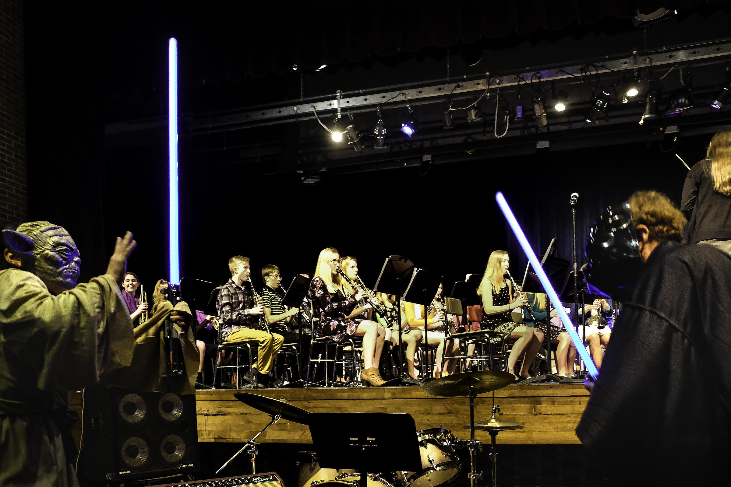 Yoda a Darth Vader light saber dual in front of band.
