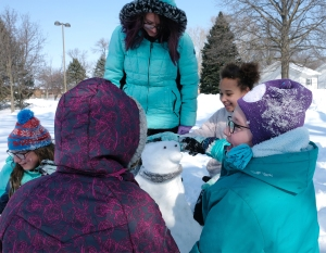 Girls build a snow penguin