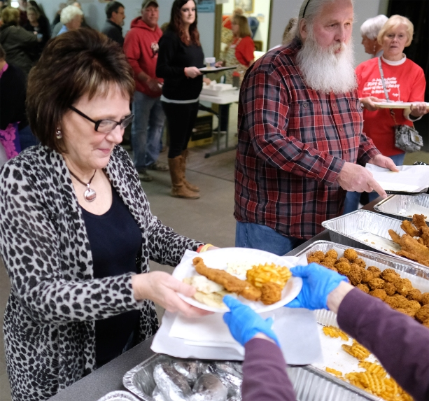 Roxanne Wieland receives her plate of baked and fried fish.