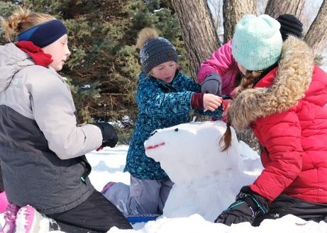 Girls build a snow dog