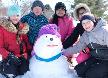 Smiling girls pose with snow dog