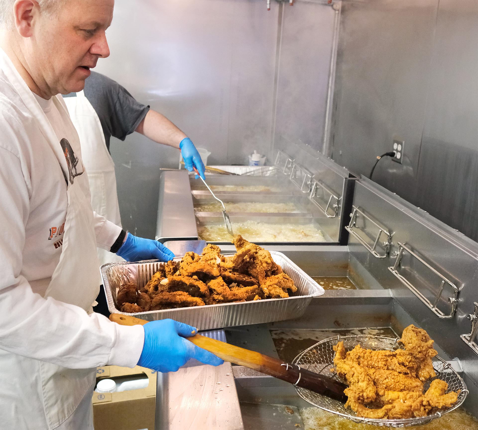 Steve Dethlefs drains a basket of hot fried fish.