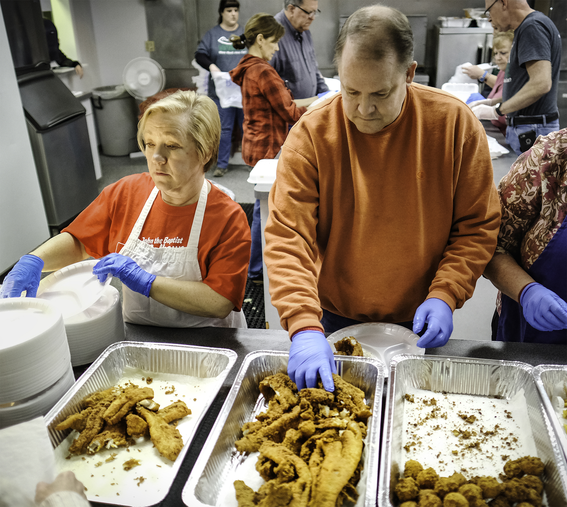 Wanda Worsley and Scott Dai serve up plates of fish.