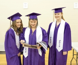 Tamrey Putnam, Maddie Probst and Brianna Satterfield look at the senior pictures in Enterprise Graduation edition.