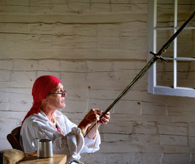 Pam Veach-Davis finger weaves a tumpline that would be attached at both ends of a back, luggage, or bedroll. Vech portrays the wife of the post trader.