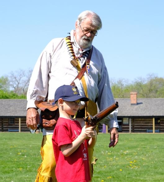 Re enactor John Mathrole watches as Owen Artz holds a 72 caliber flintlock pistol.
