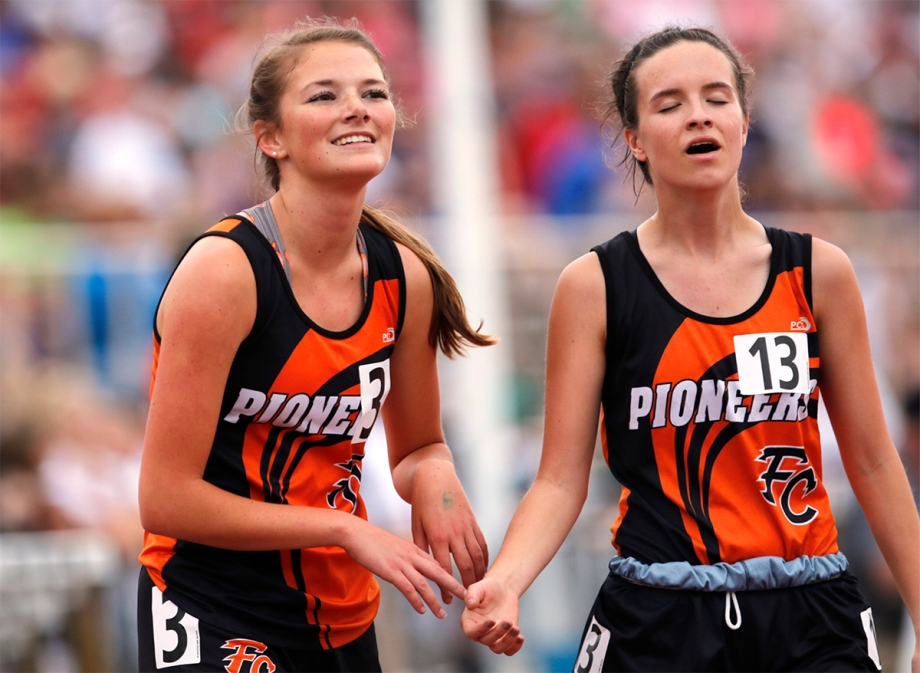 Fort Calhoun seniors Taya Skelton, left, and Avery McKennan meet at the finish line of the 3200-meter run at Omaha Burke Stadium