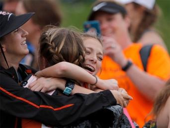 Tessa, right and Taya skelton embrace after Taya won the 3,200 meter run at Omaha Burke Stadium