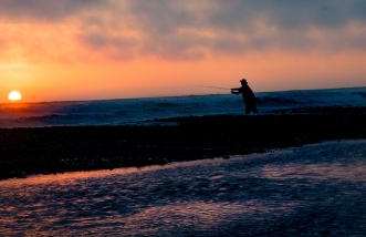 Fisherman at sunset on Kalaloch beach on the Olympic Peninsula coast.