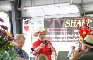 Following the re-sale of Charley Hoier's market hog, Jeff Warren takes donations in hundred dollar increments.
