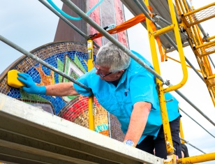 Rob Jensen applies sealant on the tower mosaic.