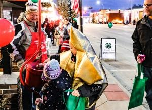 Salvation Army volunteer Paul Kolb smiles as Ivy Brandl, Alex Le Grand and Matthew Brandl put money in the bucket.