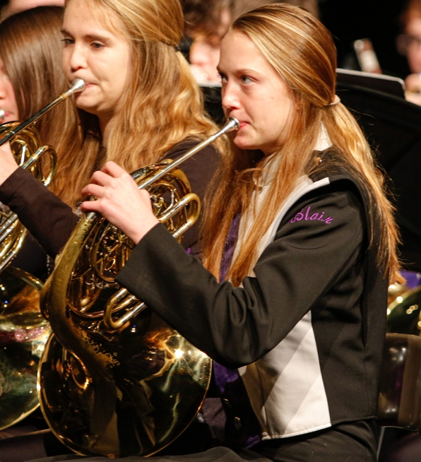 Sophomore Caitlyn Haggerstrom plays French horn in the 9-10 band during the winter concert in the Lela Neve Auditorium.