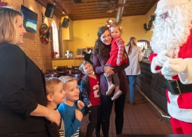 Sarah Dein with twins Jacob and Jackson and Amelia Jacobitz holding daughter Vera and with son Graham meet Santa.