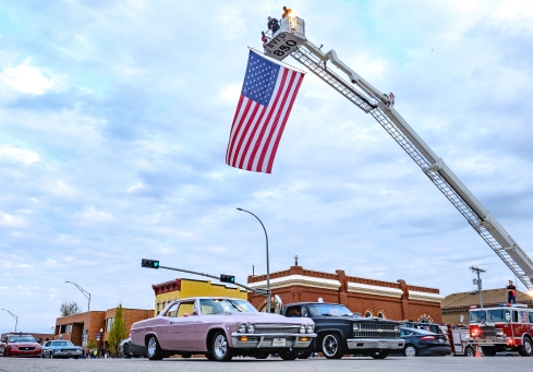 Classic cars and trucks of all kinds pass beneath the American flag on Washington Street during Cruise Night in Blair.