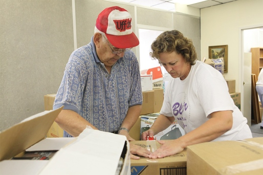 Bob Krogh and Sandra Ort Jensen tape a box of documents for transport.