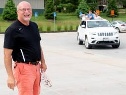 Don Johnson laughs while a caravan of vehicles parade past the entrance to Fort Calhoun High School to recognize and thank the retiring superintendant for his years of service.