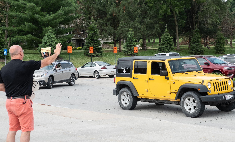 Man waves at cars in caravan
