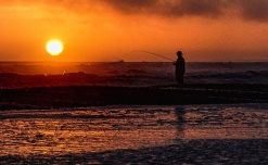 Fisherman in surf at Olympic National Forest.