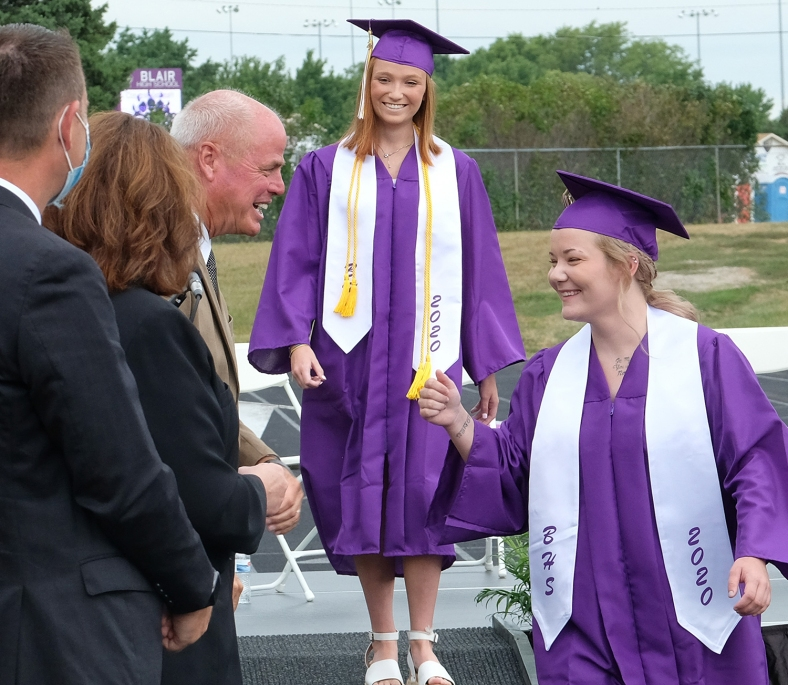 Assistant Principal Mark Gutchow greets Abby Casey followed by Sydney Chance