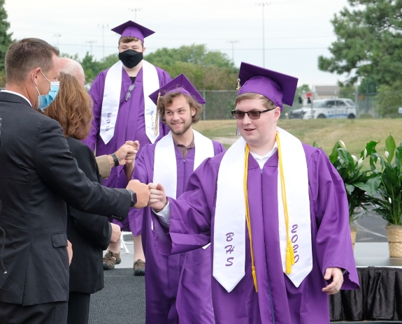 Kyle Dykstra and Brody Fetters bump fists with superintendent Randall Gilson and school board president Kari Loseke.