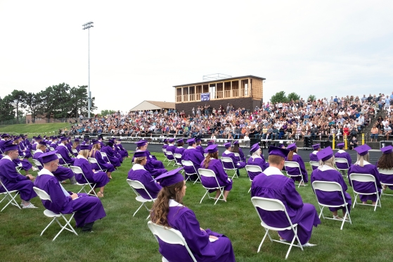 Graduating seniors are seated on the football field as commencement exercises begin.