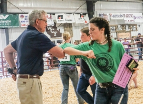 Reserve Senior Showman Ella Booth bumps elbows with judge Gary Kubicek.