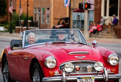 Jim Morley and wife Kathy cruise Washington Street in a vintage 60's Austin Healey convertible.